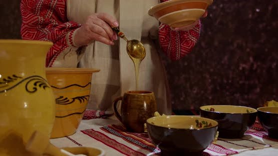 Woman In Traditional Ukrainian Embroidered Shirt Pour Honey Into Wooden Utensils
