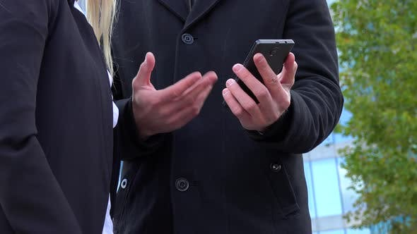 Thumbnail for A Businessman and a Businesswoman Work on a Smartphone in Front of an Office Building - Closeup