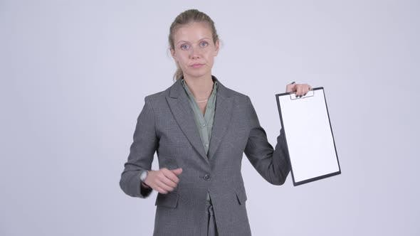Thumbnail for Young Serious Blonde Businesswoman Showing Clipboard and Giving Thumbs Down