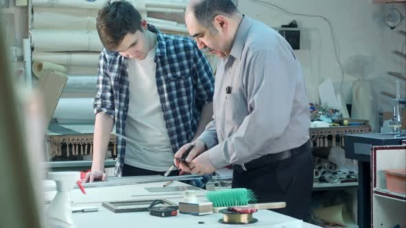 Thumbnail for Senior Male Worker Instructing Young Trainee How To Cut a Glass for Frame Behind the Desk in Frame