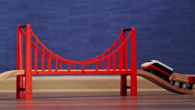 Toy Train Going Up a Red Bridge