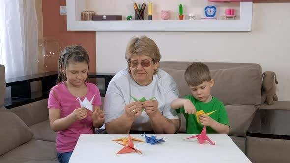 Grandmother with Children Make Paper Cranes in the Room