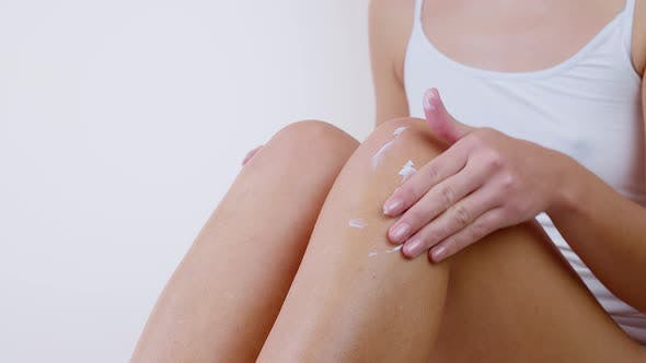 Woman Applying Moisturizer Cream or Body Lotion on Her Legs