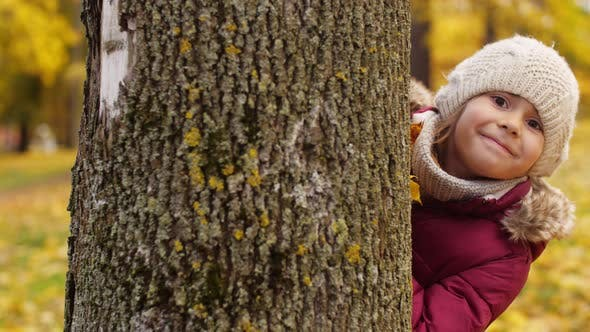 Thumbnail for Little Girl Hiding Behind Tree in Autumn