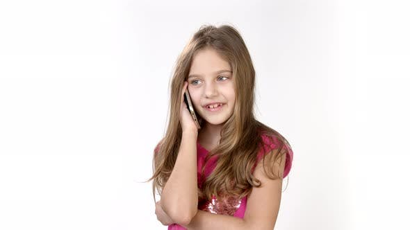 Cover Image for Emotional Conversation on the Phone of a Little Girl. A Little Girl Is on the Phone in a Bright Pink