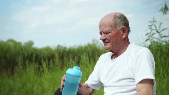 Healthy Elderly Man Restores Balance and Drinks Clean Water From a Bottle for Sports Nutrition After