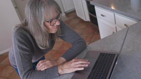 Thumbnail for Vue grand angle Senior femme blanche tapant email sur ordinateur portable dans la cuisine