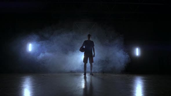 Thumbnail for The Silhouette of a Basketball Player on a Dark Background with Smoke on the Basketball Court Throws