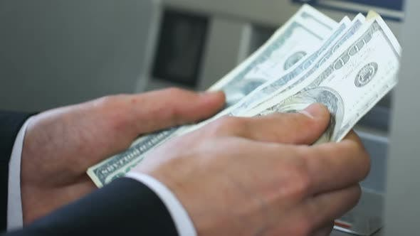 Thumbnail for Business Person Counting Dollars Near ATM and Putting Money in Wallet, Banking