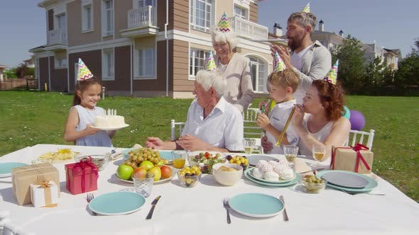Thumbnail for Little Girl Bringing Birthday Cake to Grandfather on Family Party Dinner