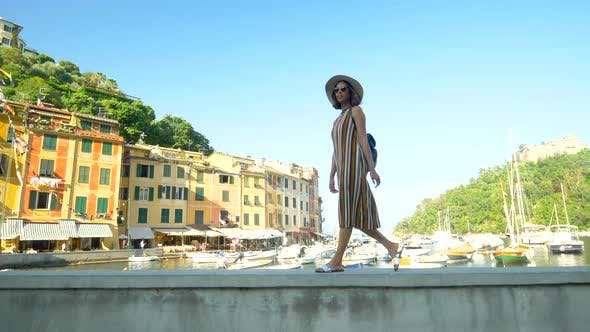 Thumbnail for A woman walking wearing hat and backpack purse traveling, Portofino, Italy, luxury resort, Europe