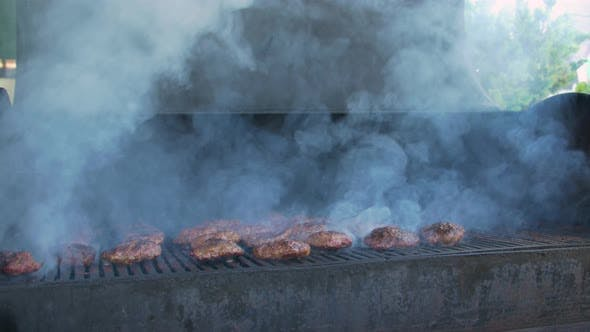 Cover Image for Cook Turns Meat On Grill