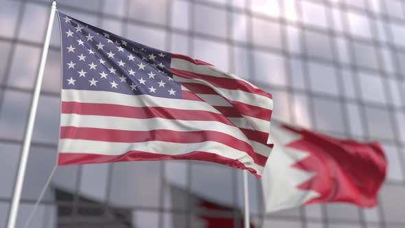 Waving Flags of the USA and Bahrain in Front of a Skyscraper