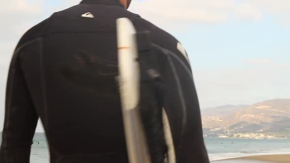 Thumbnail for A surfer looking out towards the ocean while holding his surfboard