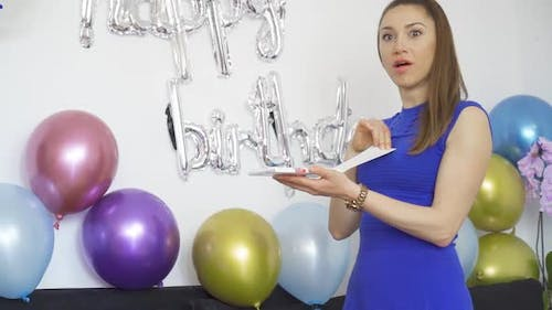 Surprised Young Woman Opening a Birthday Gift at Birthday Party with Colorful Balloons