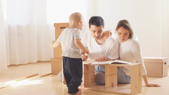 Family Together at Living Room of New Apartment Assembling Furniture, Pile of Moving Boxes on