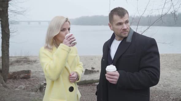 Cute Caucasian Couple Drinking Coffee and Talking on Riverbank