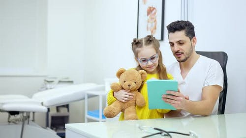 Cheerful Pediatrician and Girl Using Tablet Talking and Smiling
