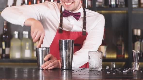 Thumbnail for Barman Wearing the Bow Tie, White Shirt and Red Apron Makes Cocktail at Bar Counter at Restaurant