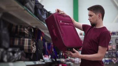 Man is Examining Suitcase in Trade Area of Store
