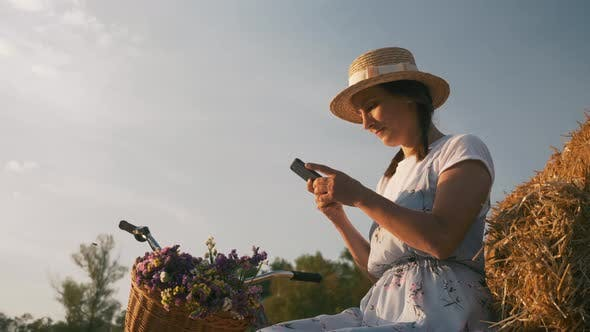 Young woman with mobile phone in hands is sitting on straw at sunset.
