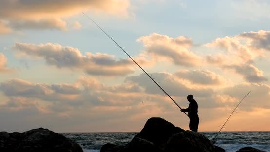 A silhouette of a fisherman at sea during sunset