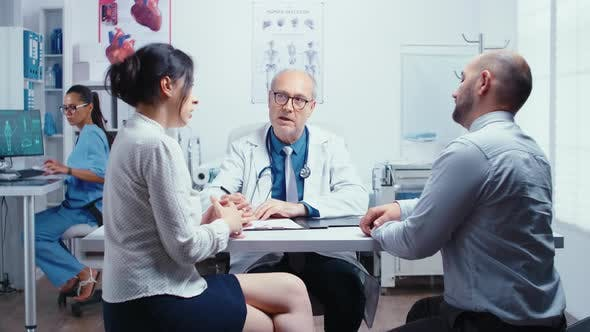Young Couple Talking with Senior Doctor