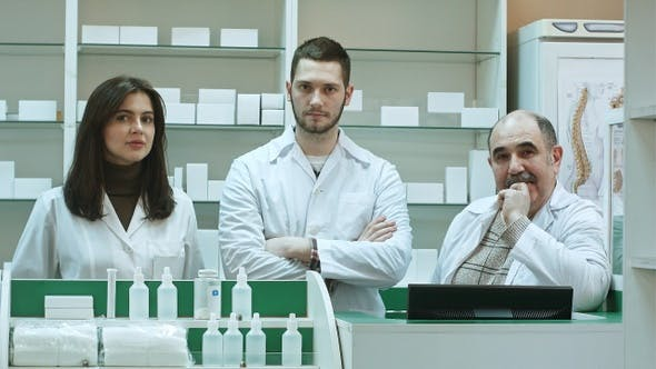 Cover Image for Positive team of pharmacists looking at camera at the hospital
