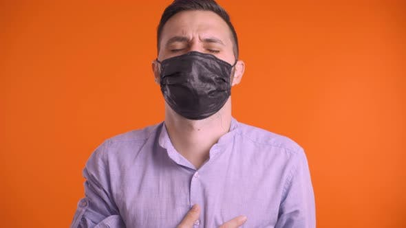 Sick Man with Black Face Mask Coughing, Removing the Mask and Breathing Freely