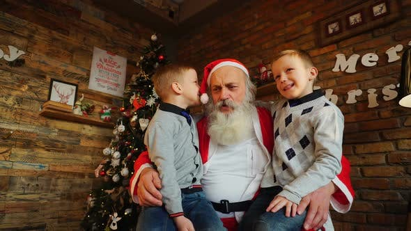 Thumbnail for Two Twin Boys Alternately Make Wish in Ear of Santa Claus in Decorated Room for Christmas