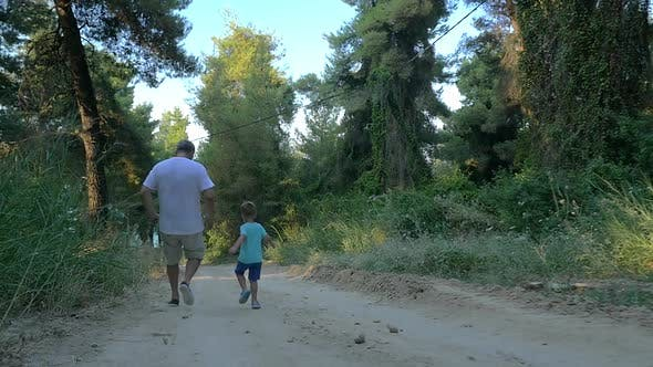 Grandson and grandfather running in the woods