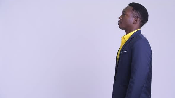 Profile View of Young Happy African Businessman Looking at Camera