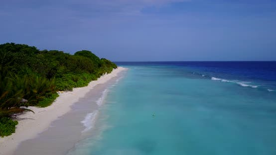 Natural above travel shot of a sandy white paradise beach and blue water background in hi res 4K