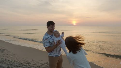 Young Family at the Sea Beach and Sunset