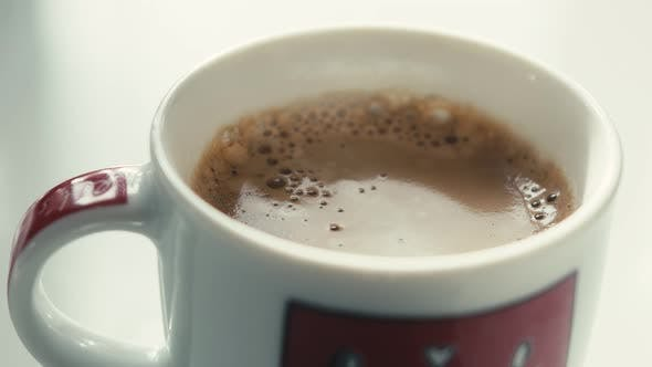 Thumbnail for Drops Falling In a Cup of Espresso in Slow Motion.