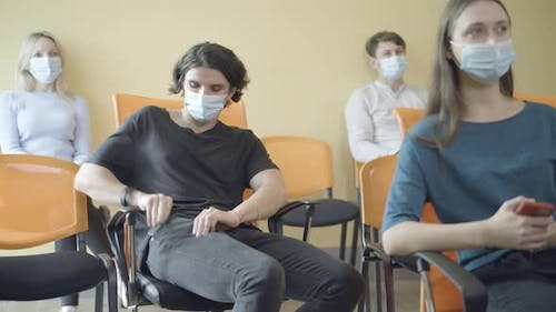 Group of Adult Caucasian People Sitting in Auditorium Listening Lecture During Covid19 Pandemic