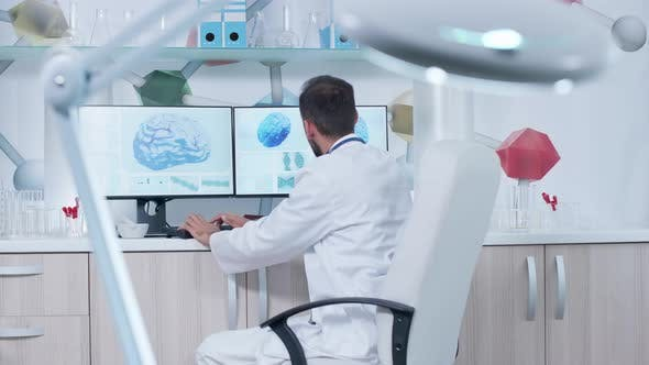 Cover Image for Doctor in Modern Office or Research Center Working on a Computer with 3D Brain Scans