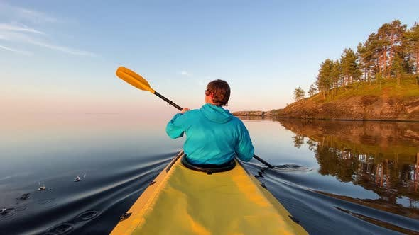 Thumbnail for man in rowing on kayak on lake on background of island at sunset, active recreation