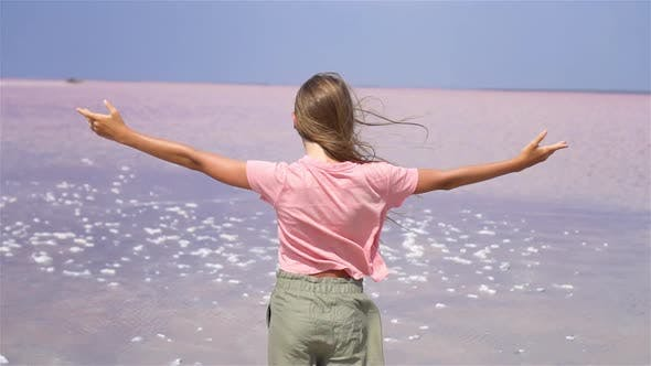 Thumbnail for Girl on a Pink Salt Lake on a Sunny Summer Day.