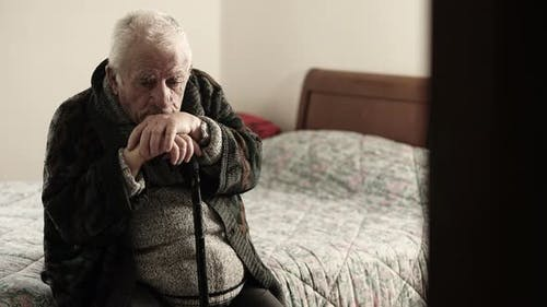 Sick Old Man Sitting on The Bed in The Nursing Home