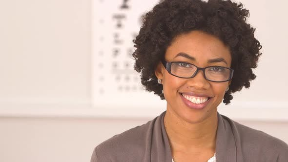 Thumbnail for African American woman happy with new glasses at eye doctor
