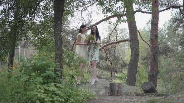 Thumbnail for Portrait Two Cute Beautiful Women in Short Summer Dresses Standing on Rocky Ground with Wild Flowers