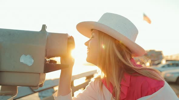 Thumbnail for Beautiful Woman Looks Through the Ocean Pier Binoculars and Smiling. Sunset, USA