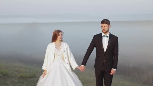 Thumbnail for Newlyweds. Caucasian Groom with Bride on the Morning Field. Fog. Wedding Couple