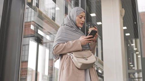 Arabic Woman Scrolling on Smartphone Indoors