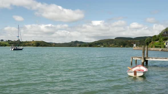 Cover Image for A rowboat and sailboat in Mangonui Harbour
