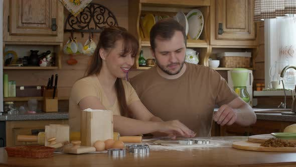 Thumbnail for A Man and a Woman Cut Out Figures for Cookies in a Dough.