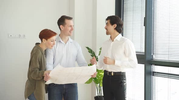 Broker or Realtor Showing Plan of New House Apartment Giving Blueprint to Customers