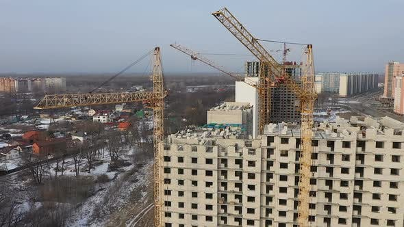 Thumbnail for Three Cranes Work on the Construction Site of a Brick High-rise. Aerial View of the Construction of