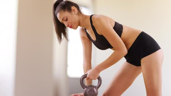 Thumbnail for A Latina girl lifts weights in the gym